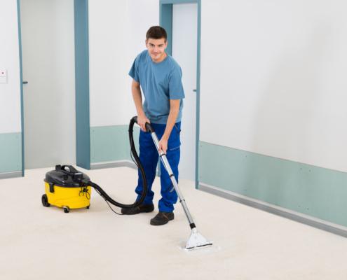 Male Cleaner Vacuuming Floor